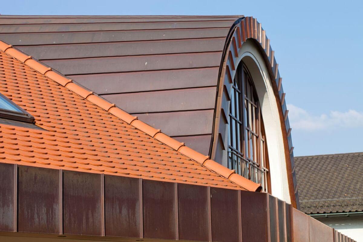 Anspruchsvolles Dach mit roten Ziegeln und Kupferblechen